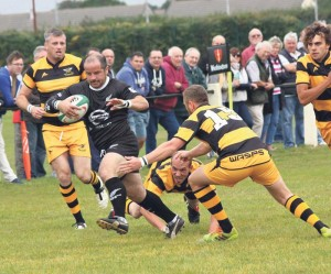 Through the Space: Neyland's Adam Collins avoids the would be Llangwm tacklers (Pic. Sheila Sear-Witts)
