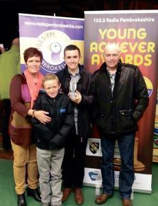 Young achiever: Sam at the awards ceremony with his family.