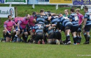 The team crouch down for a scrum: In their unfamiliar pink kit.