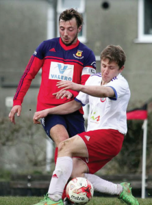 Tackle: Carew Captain Iwan Izzard comes out on top in a tackle with William Goodall (Pic Susan McKehon)