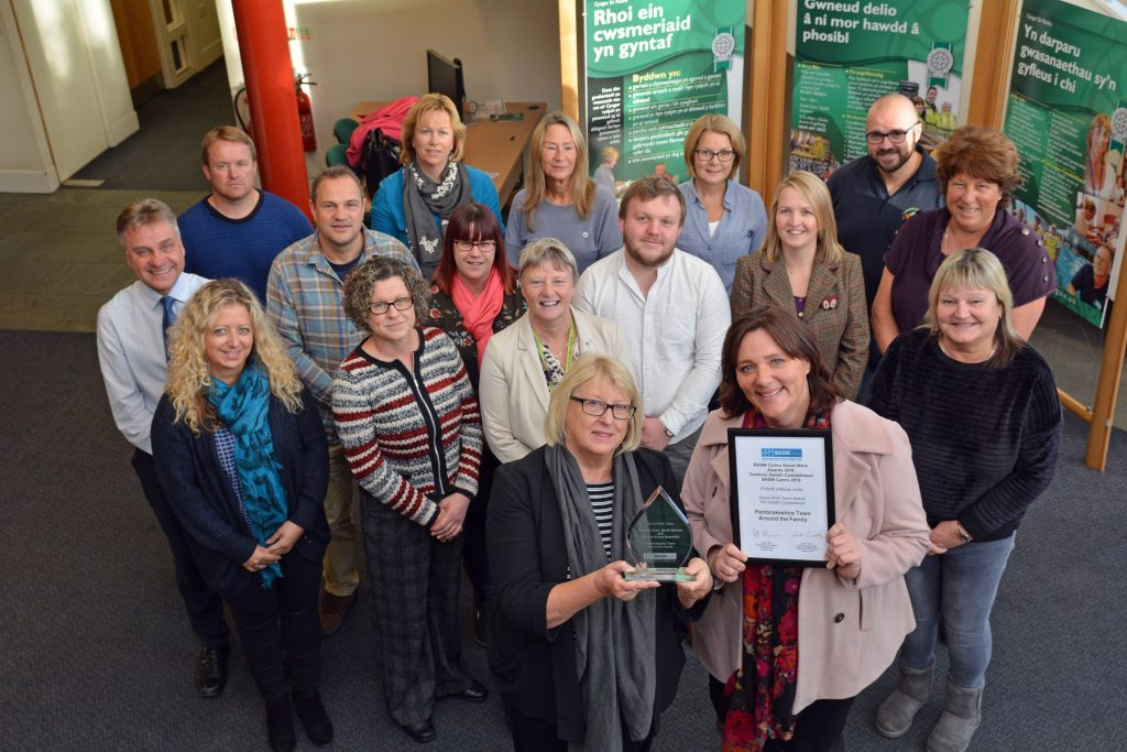 Councillor Perkins (front left) and Head of Children's Services Allison Parkinson, with the awards and the members of Team Around the Family.