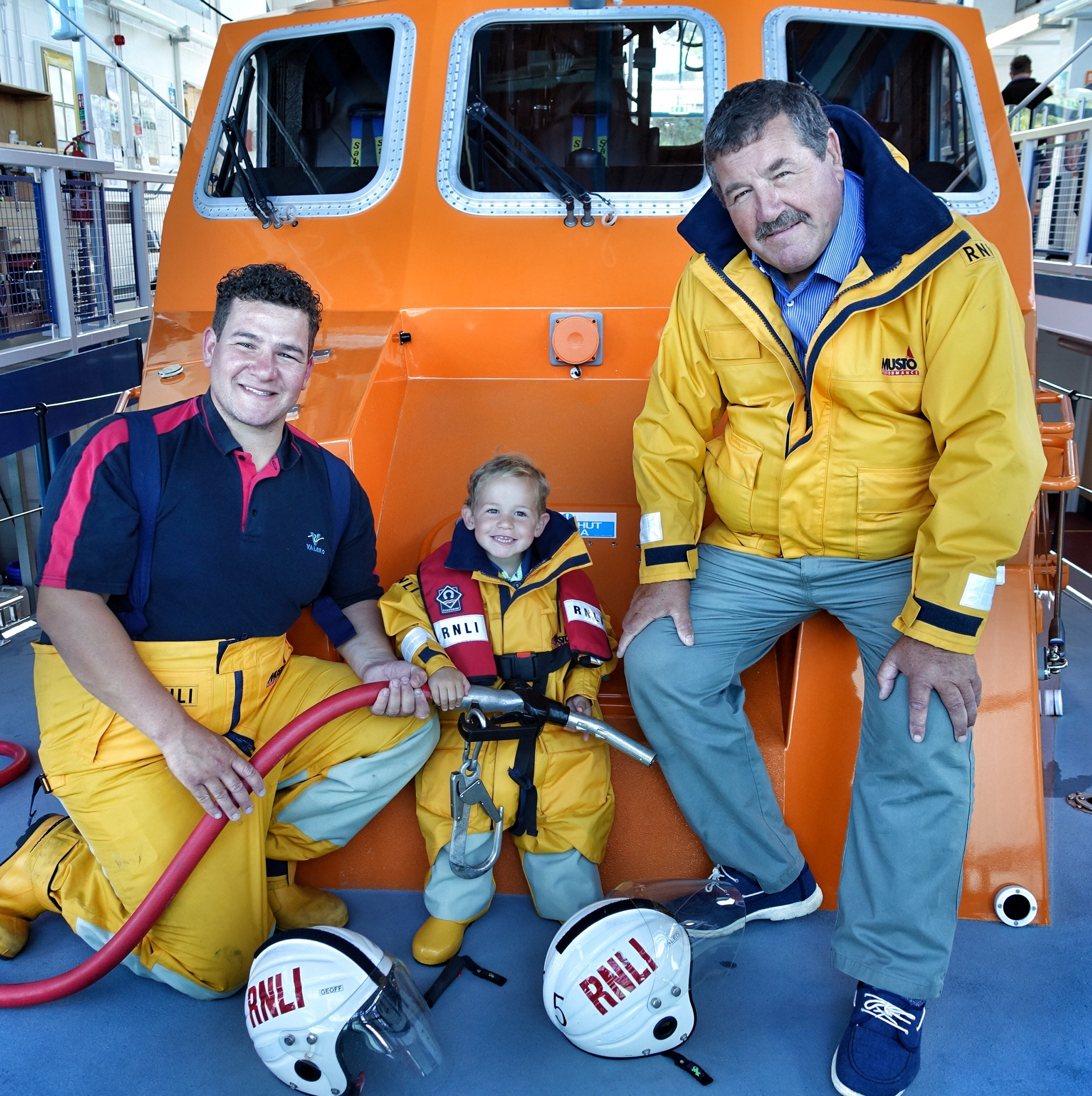 Pictured (left to right) on board Tenby RNLI's Tamar class lifeboat Haydn Miller are Tenby RNLI volunteer lifeboat crew member and Valero Pembroke Refinery worker Geoffrey Martin, his father and Tenby RNLI Deputy Launching Authority Geoffrey Martin and his two-year-old grandson Geoffrey Martin. Credit: RNLI/Tenby